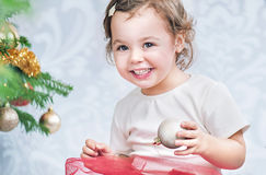 Portrait of a litle girl decorating a Christmas tree. Portrait of a litle girl decorating a fresh Christmas tree Stock Photos