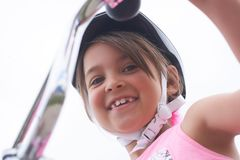 Portrait of a litte Cacasian girl in a pink safety helmet driving her bike. Portrait of a litte smiling girl in a pink safety helmet driving her bike. Safe stock photos