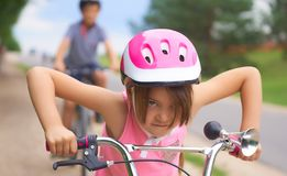 Portrait of a litte girl in a pink safety helmet driving her bike. Safe movement of bicycles on the roads royalty free stock images