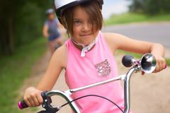 Portrait of a litte girl in a pink safety helmet driving her bike. Safe movement of bicycles on the roads stock photography