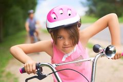 Portrait of a litte girl in a pink safety helmet driving her bike. Safe movement of bicycles on the roads stock images