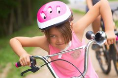 Portrait of a litte girl in a pink safety helmet driving her bike. Safe movement of bicycles on the roads stock photos