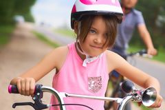 Portrait of a litte girl in a pink safety helmet driving her bike. Safe movement of bicycles on the roads royalty free stock photo