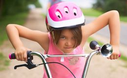Portrait of a litte girl in a pink safety helmet driving her bike. Safe movement of bicycles on the roads stock photo