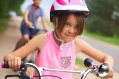 Portrait of a litte girl in a pink safety helmet driving her bike. Safe movement of bicycles on the roads stock image