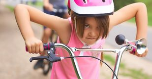 Portrait of a litte girl in a pink safety helmet driving her bike. Safe movement of bicycles on the roads royalty free stock photos