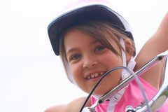 Portrait of a litte Cacasian girl in a pink safety helmet driving her bike. Portrait of a litte smiling girl in a pink safety helmet driving her bike. Safe royalty free stock image