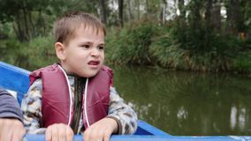 Portrait of little adorable child holds paddle. Close up view of little cute boy smiling at camera on lake. Happy child holds padd stock video footage