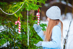 Portrait of little adorable girl in blue coat and mittens standing near the decorated Christmas tree on frosty winter Royalty Free Stock Photo