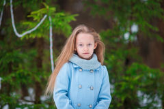 Portrait of little adorable girl in blue coat and mittens standing near the decorated Christmas tree on frosty winter Stock Photo