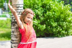 Portrait of little adorable girl with flowers in Royalty Free Stock Photo