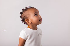 Portrait of little African American little girl playing with soa Royalty Free Stock Photo