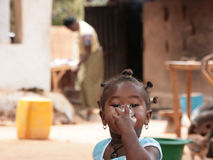 Portrait of a little African girl drinking. Little African girl looking into the camera while covering her mouth with a drinking glass. Her mother and the Stock Photo