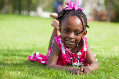 Portrait of a little african girl  lying down  Stock Photo