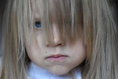 Portrait of a little angry girl with her hair loose on her face. Portrait of little angry girl with her hair loose on her face Stock Photo