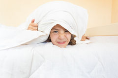 Portrait of little angry girl lying in bed with pillow on head Stock Images
