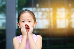 Portrait little Asian child girl acting and shouting through hands like megaphone. Communication concept stock image