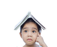 Portrait of little Asian child thinking and put a book on top. On white background stock photo