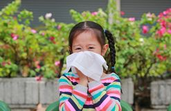Portrait little Asian girl blowing her nose with tissue paper sitting outdoor royalty free stock image