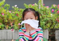 Portrait little Asian girl blowing her nose with tissue paper sitting outdoor stock photos