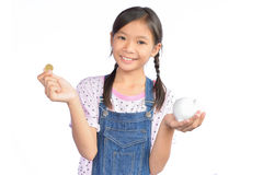 Portrait of little Asian girl holding piggy bank on white. Background Stock Images