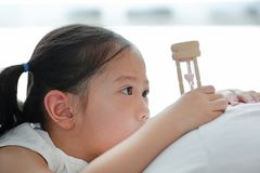 Portrait of little Asian girl looking at hourglass in hand lying on bed at home. Waiting times with sandglass. Close-up shot royalty free stock image