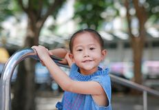 Portrait of little asian girl playful hanging at metal stair royalty free stock images