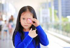 Portrait of little Asian girl playing with toy camera to take pictures outdoor. Kid development concept royalty free stock photos