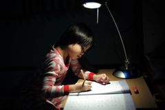 Portrait of little Asian girls doing her homework under the lighting lamp. In a dark room royalty free stock photos