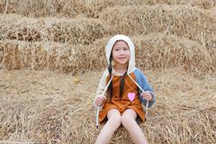Portrait of little Asian kid girl in a hood on head and warm clothes sitting on pile of straw on a winter season.  royalty free stock photos