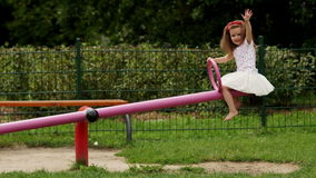 Portrait of Little Attractive Girl in White Skirt and Shirt, with Red Flowers on Her Head Sitting on the Seesaw and stock footage