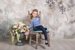 Portrait of a little attractive smiling girl in a blue sweater and pants with her hair folded in her hair sitting on a chair royalty free stock images