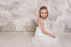 Portrait of a little attractive smiling girl in a white dress with curled hair against the background of a grunge wall stock photos