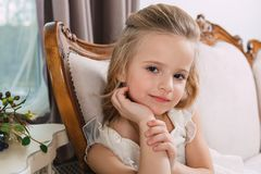 Portrait of a little attractive smiling girl in a white dress with curled hair against the background of a grunge wall royalty free stock image