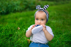 Portrait of a little baby chews his shoe on a grass. Portrait of a little baby in white shirt chews his shoe on a green grass Stock Photos