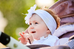Portrait of the little baby girl sitting in a children`s carriage in summer day. Cute baby girl in the white dress and with bow. Horizontal photo and close-up Royalty Free Stock Images