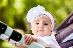Portrait of the little baby girl sitting in a children`s carriage in summer day. Cute baby girl in the white dress and with bow. Horizontal photo and close-up Stock Photos