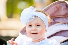 Portrait of the little baby girl sitting in a children`s carriage in summer day. Cute baby girl in the white dress and with bow. Horizontal photo and close-up Stock Photography