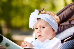 Portrait of the little baby girl sitting in a children`s carriage in summer day. Cute baby girl in the white dress and with bow. Horizontal photo and close-up Royalty Free Stock Photos