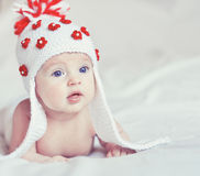 Portrait of little baby with knitted hat. Portrait of little infant lying on the bed Royalty Free Stock Image