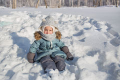 Portrait of little baby sits on snow in winter Stock Photos