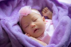 Portrait of little baby sleeping on the purple bed royalty free stock photos