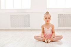 Portrait of little ballerina on floor, copy space. Smiling baby girl dreaming to become professional ballet dancer, classical dance school Royalty Free Stock Images