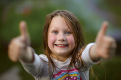 Portrait of little  beautiful and confident girl showing thumbs Royalty Free Stock Photo