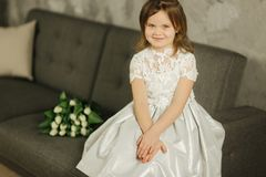 Portrait of little beautiful girl hold a bouquet of flowers at home. She sist on sofa at home and waiting for her mom. Beautiul little girl hold a bouquet of royalty free stock image
