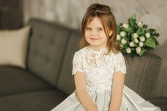 Portrait of little beautiful girl hold a bouquet of flowers at home. She sist on sofa at home and waiting for her mom. Beautiul little girl hold a bouquet of stock photos