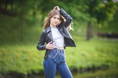 Portrait of little beautiful stylish kid girl in blue jeans and leather jacket in city park on green forest background.  royalty free stock photos