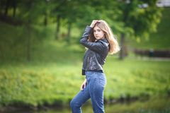 Portrait of little beautiful stylish kid girl in blue jeans and leather jacket in city park on green forest background.  stock photography