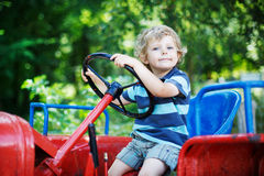 Portrait of little blond boy in tractor in summer Royalty Free Stock Photos