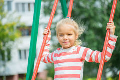 Portrait of a little blond girl on swing Stock Photo